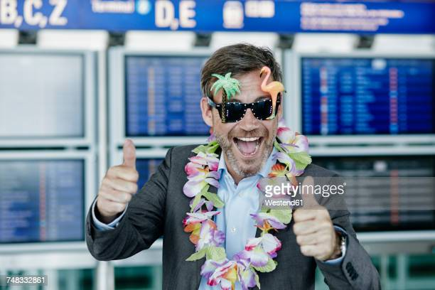 happy businessman dressed up as tourist at the airport - practical joke stock photos and pictures