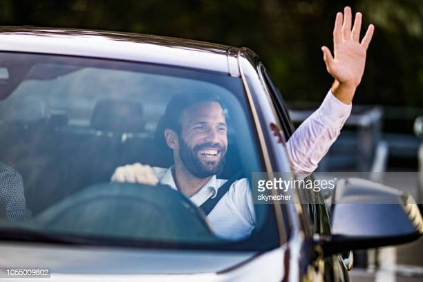 happy businessman driving a car and waving to someone. - waving stock pictures, royalty-free photos & images