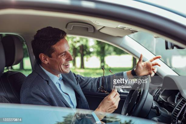 happy businessman during a hands free conversation in his car - bluetooth stock pictures, royalty-free photos & images