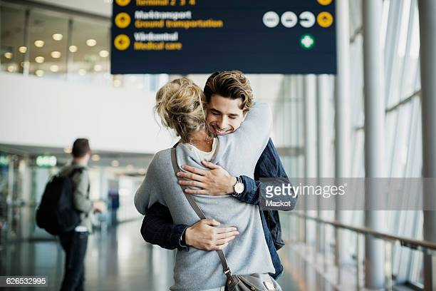 happy businessman embracing colleague at airport - embracing stock pictures, royalty-free photos & images
