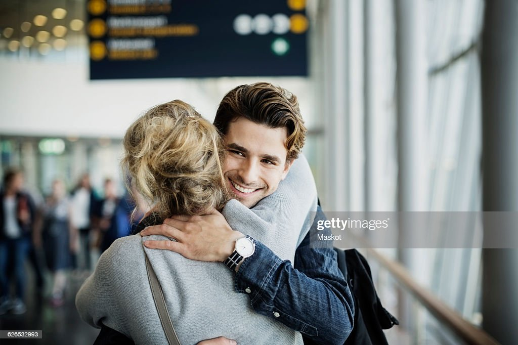 Happy businessman embracing female colleague at airport : Stock Photo