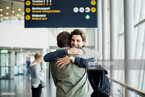Happy businessman embracing male colleague at airport
