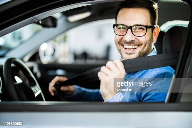 happy businessman fastening seatbelt before his trip by car. - car stock pictures, royalty-free photos & images