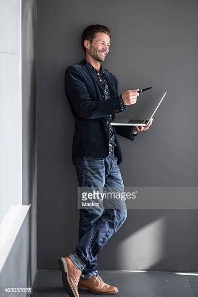 Happy businessman gesturing with pen while holding laptop against wall