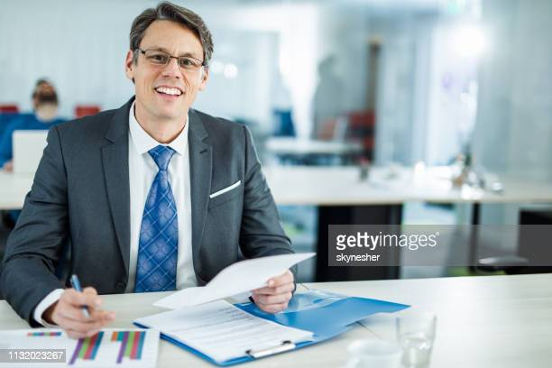 happy businessman going through financial reports in the office. - bank manager stock pictures, royalty-free photos & images