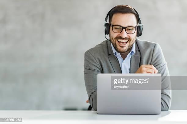 オフィスでラップトップ上のビデオ通話を持っている幸せなビジネスマン。 - ウェブ会議 ストックフォトと画像