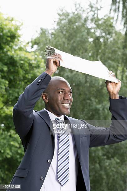 Happy businessman holding newspaper above head