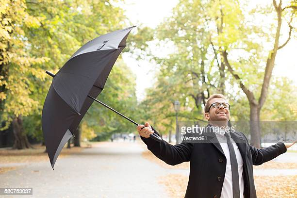 Happy businessman in a park with umbrella after rain