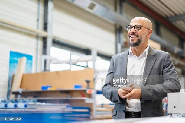 happy businessman in factory - finanzen und wirtschaft stock-fotos und bilder