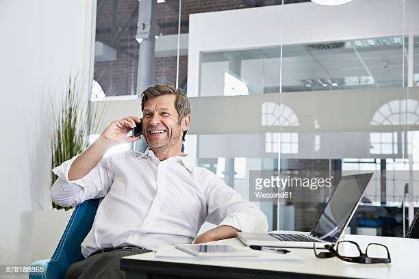 Happy businessman in office on smartphone
