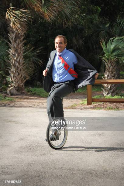 happy businessman in suit riding a unicycle - fauci stock pictures, royalty-free photos & images
