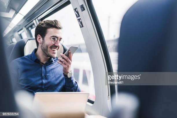 happy businessman in train using cell phone - eisenbahn stock-fotos und bilder