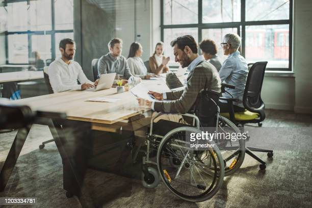 glücklicher geschäftsmann im rollstuhl liest dokumente während eines treffens mit seinen kollegen. - persons with disabilities stock-fotos und bilder