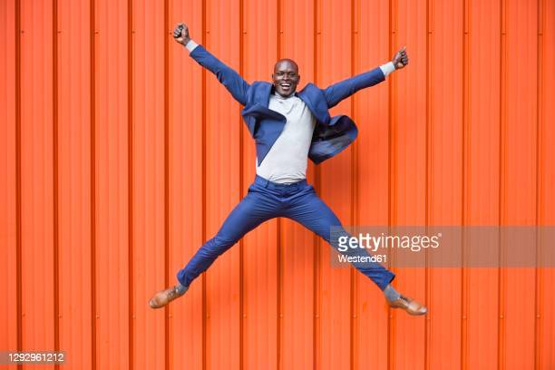 happy businessman jumping in the air in front of orange wall - menswear stock pictures, royalty-free photos & images