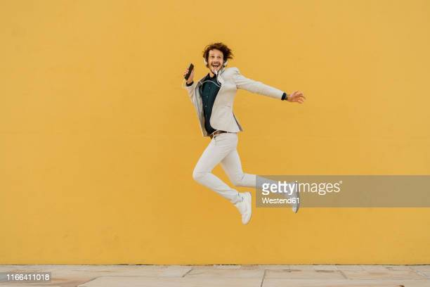 happy businessman jumping in the air in front of yellow wall listening music with headphones - alegria imagens e fotografias de stock