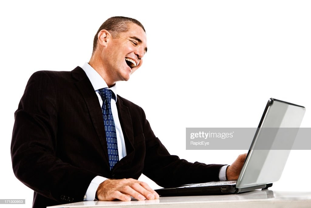 Happy businessman laughs at something on his laptop : Stock Photo
