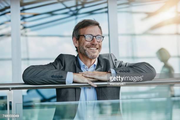 happy businessman leaning on railing at the airport - geländer stock-fotos und bilder