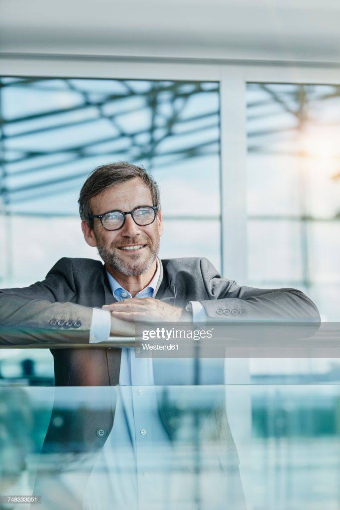 happy businessman leaning on railing at the airport stock photo