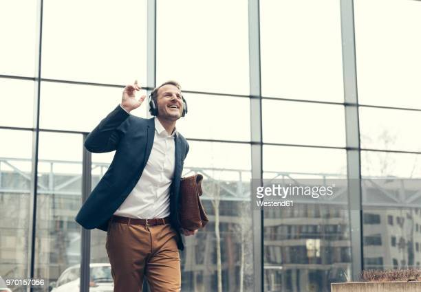 happy businessman listening to music with headphones - after work stock pictures, royalty-free photos & images