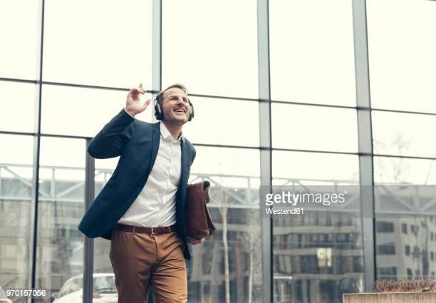 happy businessman listening to music with headphones - feierabend stock-fotos und bilder