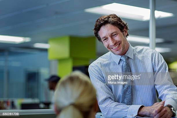 Happy businessman looking at colleague