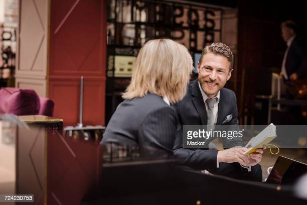Happy businessman looking at female partner during meeting in hotel reception