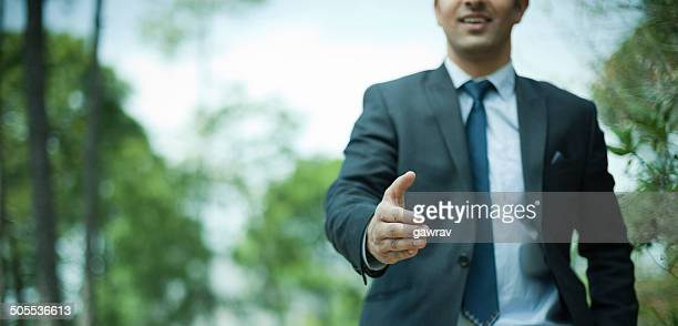 Happy businessman offering for handshake in nature.
