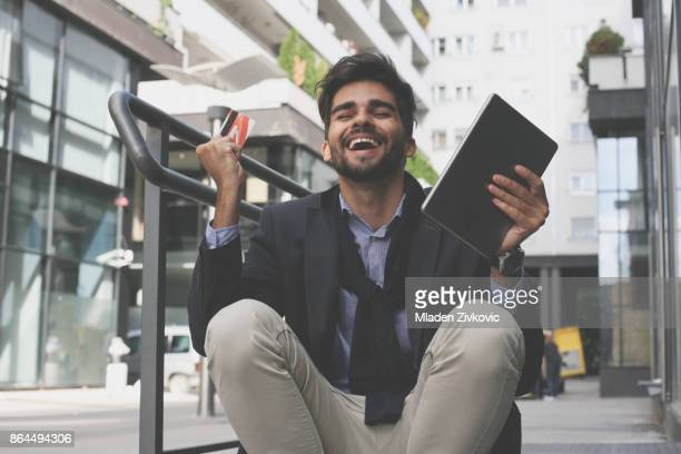 Happy businessman on street  using credit card and iPod and receiving good news.