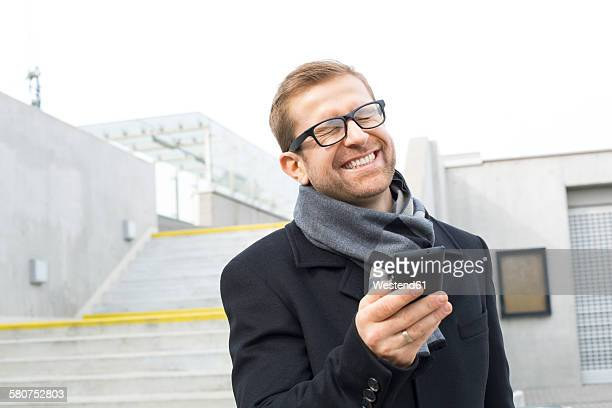happy businessman outdoors holding cell phone - squinting stock photos and pictures