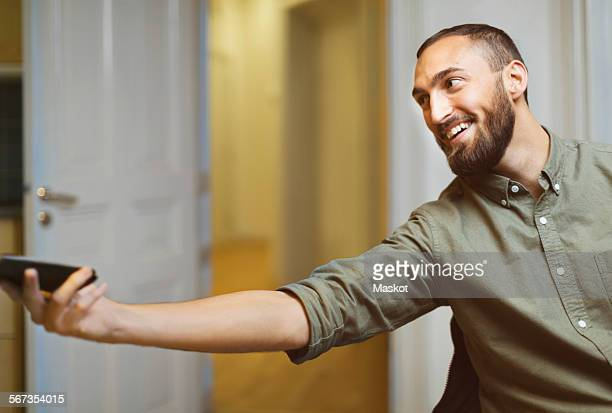 Happy businessman passing mobile phone in office