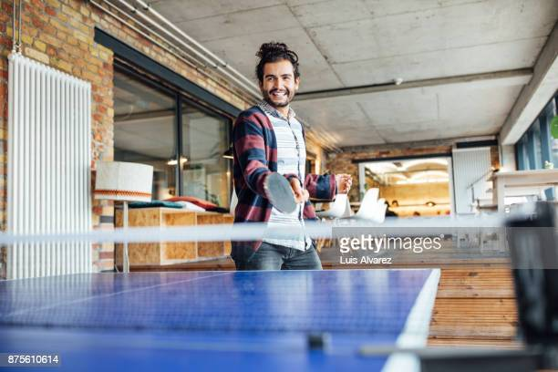 Happy businessman playing table tennis