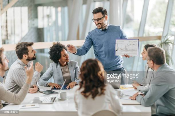 happy businessman presenting his colleagues new reports on a meeting in the office. - blockchain stock pictures, royalty-free photos & images