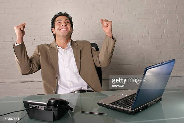 Happy businessman raising his fists in the air at an office