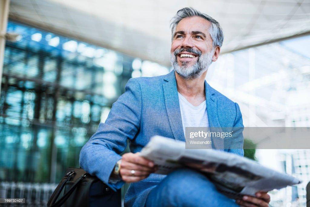 Happy businessman reading newspaper : Stock-Foto