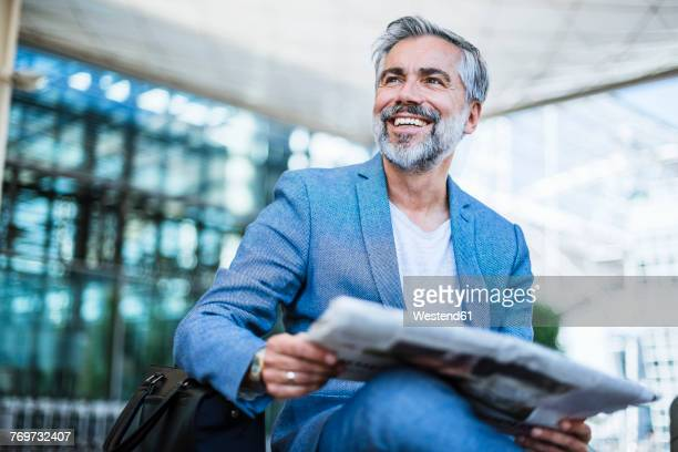 Happy businessman reading newspaper