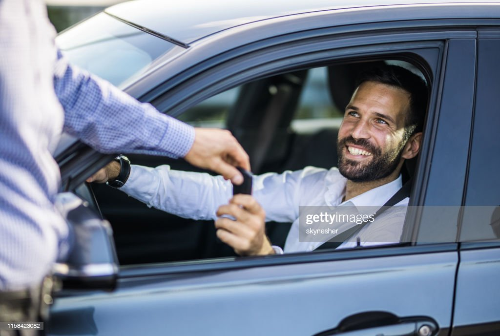 Happy businessman receiving keys of his new car. : Stock Photo