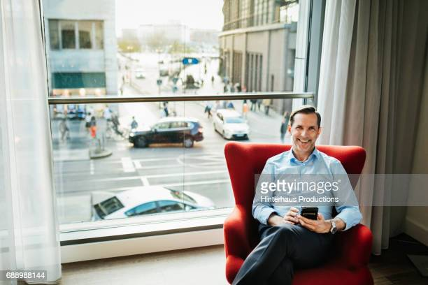 Happy Businessman Relaxing in Hotel Room