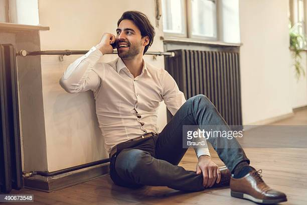 Happy businessman relaxing on floor while talking on cell phone.