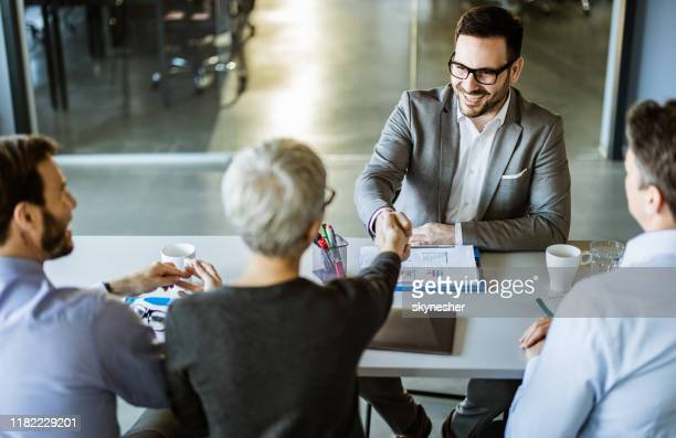 happy businessman shaking hands with member of human resource team in the office. - human resources stock pictures, royalty-free photos & images