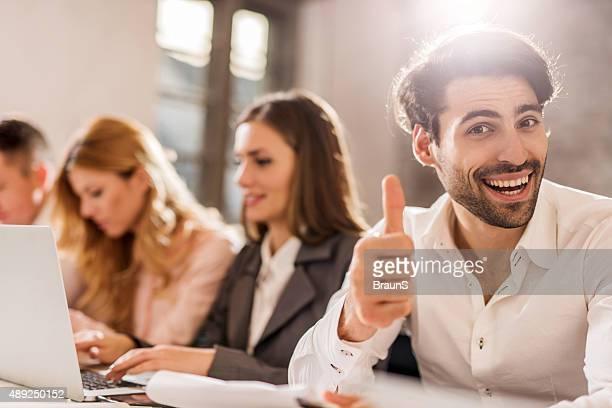 Happy businessman showing ok señal en una reunión.