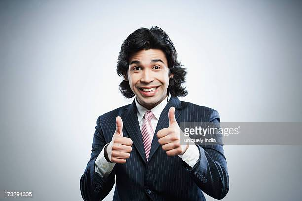 Happy businessman showing thumbs up sign