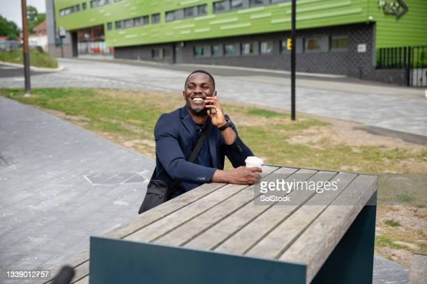 happy businessman sitting at an outdoor table - green blazer stock pictures, royalty-free photos & images
