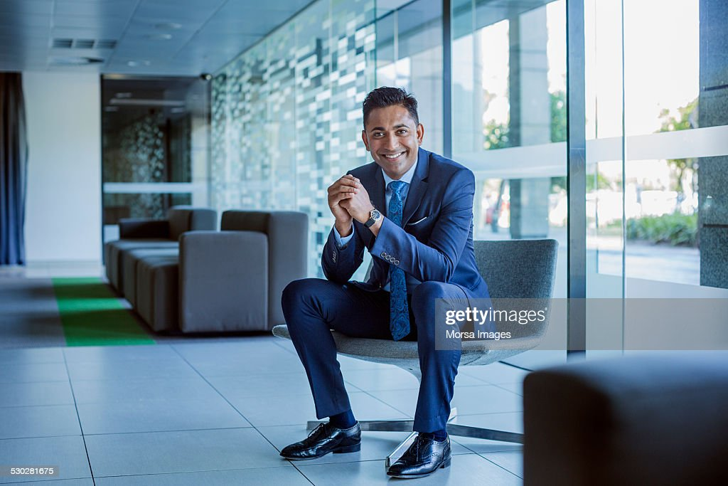 Happy businessman sitting in office lobby : Photo