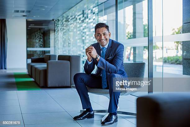 happy businessman sitting in office lobby - traje completo - fotografias e filmes do acervo