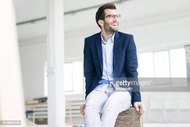 happy businessman sitting on crate in empty loft office - mercado espacio de comercio fotografías e imágenes de stock