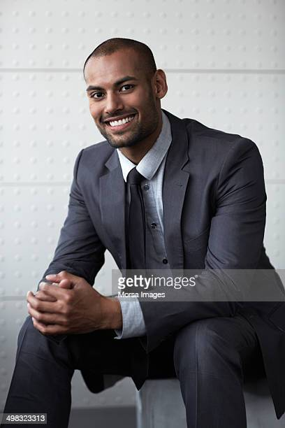 Happy businessman sitting with hands clasped