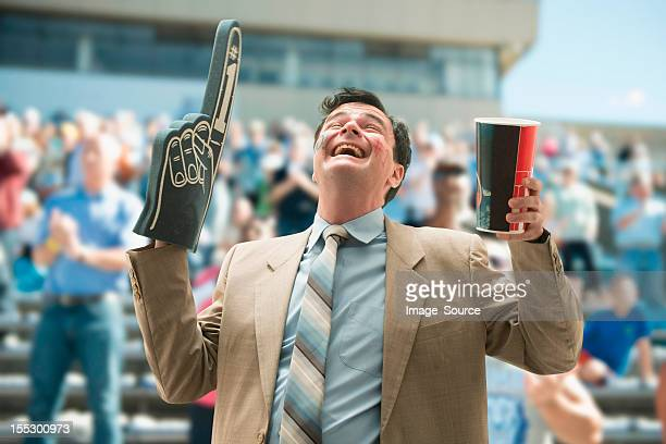 happy businessman sports fan with foam hand and drink - fan enthusiast stock photos and pictures