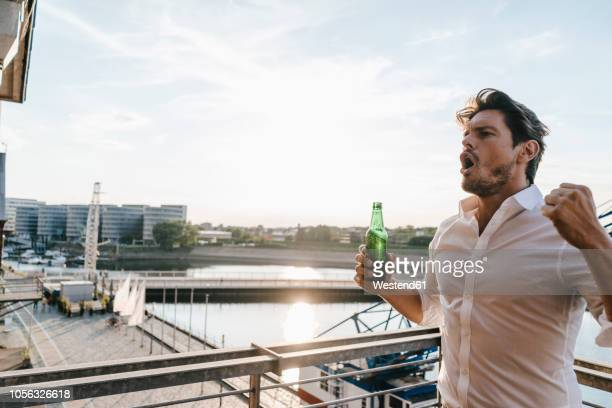 happy businessman standing on balcony, drinking beer - ruhr stock pictures, royalty-free photos & images