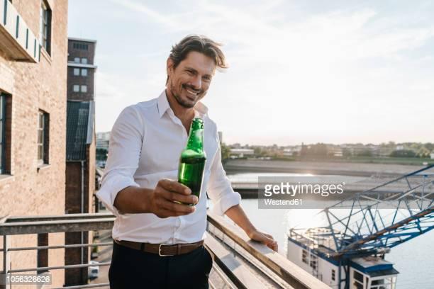 happy businessman standing on balcony, drinking beer - feierabend stock-fotos und bilder