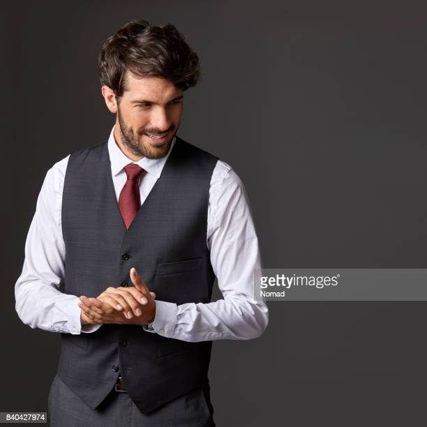 happy businessman standing with hands clasped - waistcoat stock photos and pictures